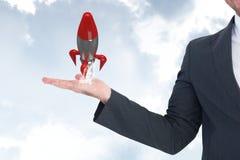 Biznesowy mężczyzna trzyma rakietę przeciw niebu Zdjęcia Stock