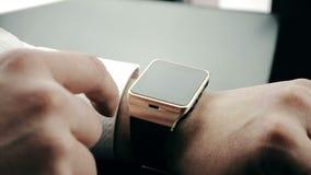 Biznesowy mężczyzna używa jego smartwatch app w biurze zbiory
