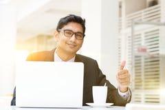 Biznesowy mężczyzna używa laptop przy cukiernianym kciukiem up Obrazy Stock
