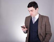 Biznesowy mężczyzna używa mądrze telefon nad popielatym Obraz Royalty Free