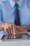 Biznesowy mężczyzna używa pastylki compuer przy biurem Zdjęcie Royalty Free