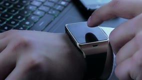 Biznesowy mężczyzna używa smartwatch app blisko komputeru osobistego smartphone i klawiatury zbiory