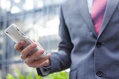 Biznesowy mężczyzna używa telefon komórkowego (ostrość na telefonie komórkowym) zdjęcia royalty free