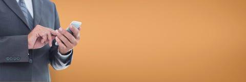 Biznesowy mężczyzna używa telefon przeciw pomarańczowemu tłu Fotografia Royalty Free
