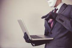 Biznesowy mężczyzna w biel maskowych jest ubranym rękawiczkach i używać komputerze - oszustwo, hacker, kradzież, cyber przestępst zdjęcie royalty free