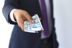 Biznesowy mężczyzna w kostiumu daje 100 zeluje rachunki, peruvian waluty pojęcie fotografia stock