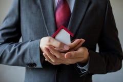 Biznesowy mężczyzna w kostiumu używać ręki zakrywa dom i ochrania Zdjęcia Stock