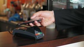 Biznesowy mężczyzna w kurtce przy kawiarnią płaci cenę używać terminal i smartphone zbiory