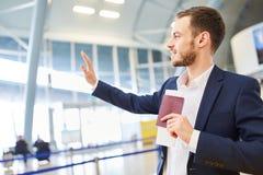 Biznesowy mężczyzna w lotniskowym falowaniu do widzenia fotografia stock