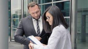 Biznesowy mężczyzna wita młodej kobiety przy wejściem budynek biurowy zdjęcie wideo