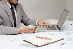 Biznesowy mężczyzna wręcza telefon komórkowego, laptop, pióro i notatnika ruchliwie używa, przy biurowym biurkiem Analiza wykresy obrazy stock