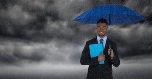 Biznesowy mężczyzna z parasolową i błękitną książką przeciw burz chmurom z deszczem Fotografia Royalty Free