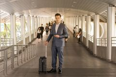 Biznesowy mężczyzna z podróży torby use mądrze telefonem na spaceru sposobu dowcipie Obraz Royalty Free