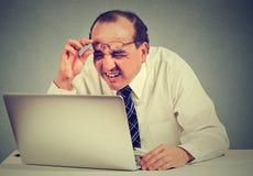 Biznesowy mężczyzna z szkłami ma wzrok problemy wprawiać w zakłopotanie z laptopu oprogramowaniem Obrazy Royalty Free