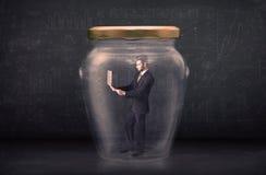 Biznesowy mężczyzna zamykał w szklanego słoju pojęcie Fotografia Stock