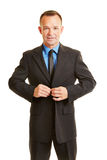 Biznesowy mężczyzna zapina w górę jego kostiumu zdjęcie stock