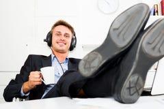Biznesowy męski pracownik relaksuje z muzyką w hełmofonach Zdjęcia Royalty Free