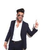 Biznesowy mężczyzna jest ubranym okulary przeciwsłonecznych ono uśmiecha się up i wskazuje Obrazy Stock