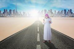 Biznesowy muzułmański używa smartphone na drodze Obrazy Royalty Free