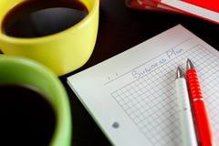 Biznesowy planowanie z kawą, notatnikiem, sketchbook i dwa piórem na ciemnego brązu drewnianym stole, Fotografia Royalty Free