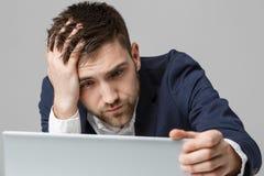 Biznesowy pojęcie - portreta przystojny stresujący biznesowy mężczyzna patrzeje pracę w laptopie w kostiumu szoku Biały tło Obraz Royalty Free