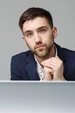 Biznesowy pojęcie - portreta przystojny stresujący biznesowy mężczyzna patrzeje pracę w laptopie w kostiumu szoku Biały tło Fotografia Stock