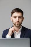 Biznesowy pojęcie - portreta przystojny stresujący biznesowy mężczyzna patrzeje pracę w laptopie w kostiumu szoku Biały tło Fotografia Royalty Free