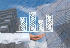 Biznesowy prętowy wykres rysujący na mężczyzna ręce i drapaczy chmur półdupkach ręka Zdjęcia Royalty Free