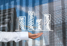 Biznesowy prętowy wykres rysujący na mężczyzna ręce i drapaczy chmur półdupkach ręka Fotografia Royalty Free