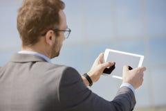 Biznesowy profesjonalista używa cyfrowego pastylka przyrząd z daleko Zdjęcie Royalty Free