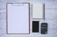 Biznesowy przedmiota pojęcie, Nowy smartphone i puste miejsce notatnik z pustym papierem na drewnianym schowku, Zdjęcia Stock