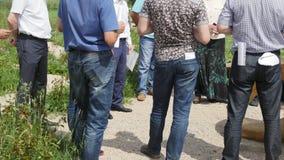 Biznesowy spotkanie plenerowy - rządowe pracodawcy lub biznesmeni opowiada przy słonecznym dniem w polu zdjęcie wideo