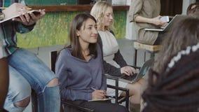 Biznesowy spotkanie przy nowożytnym modnym biurem Młoda wieloetniczna drużyna słucha konwersatorium Uczeń robi notatkom przy lapt zdjęcie wideo