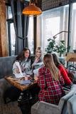 Biznesowy spotkanie w kawiarni, cztery młodej kobiety siedzi przy stołem i dyskutuje dokumenty Obrazy Stock