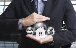 Biznesowy sprzedawca ręki mienia dom, samochód, rodzina Obrazy Royalty Free