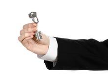 Biznesowy temat: agent nieruchomości w kurtce w jego ręce klucz nowy mieszkanie na białym odosobnionym tle Zdjęcia Royalty Free