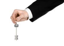 Biznesowy temat: agent nieruchomości w kurtce w jego ręce klucz nowy mieszkanie na białym odosobnionym tle Fotografia Royalty Free
