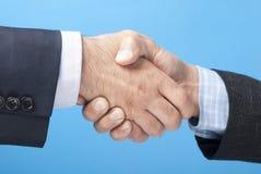 Biznesowy uścisk dłoni nad błękitnym tłem Zdjęcia Royalty Free