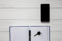 Biznesowy ustawiający notatka, telefon komórkowy i klucz na białym drewnianym tle, Zdjęcia Royalty Free