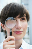 Biznesswoman with magnifier. The business woman with a magnifier in hands Royalty Free Stock Photos