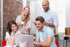 Biznesu drużynowy śmiać się wpólnie przed laptopem Obrazy Royalty Free