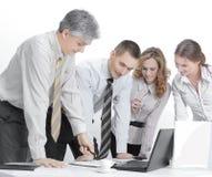 Biznesu drużynowy działanie podczas gdy dyskutujący pieniężnych dokumenty, stoi blisko desktop Fotografia Stock
