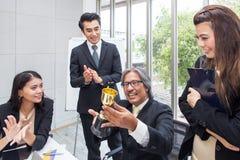 Biznesu drużynowy wygrany trofeum w biurze Biznesmen z te obrazy royalty free