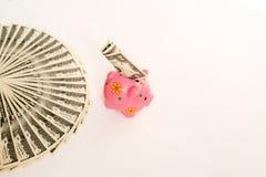 Biznesu, finanse, inwestyci, oszczędzania i korupci pojęcie, - zamyka up dolar gotówki pieniądze i prosiątko bank na stole obraz stock
