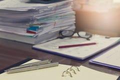 Biznesu i finanse pojęcie biurowy działanie, stos niedokończeni dokumenty na biurowym biurku, zbliżenia piórze i ołówku z stertą, Fotografia Stock