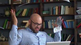 Biznesu, ludzi, sukcesu i pomyślności pojęcie, - szczęśliwy biznesmen z dolarowym pieniądze i laptopu obsiadaniem przy stołem zbiory wideo
