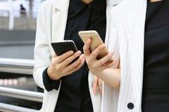 Bizneswomanów partnery patrzeje mądrze telefon Zdjęcie Royalty Free