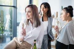 Bizneswomanów pić szampański daleko od i patrzeć w biurze Obrazy Royalty Free