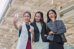 Bizneswomanów przyjaciół selfie z smartphone i wskazywać przy ekranem zaskakującym Obrazy Royalty Free