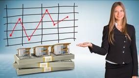 Bizneswomanów punktów ręka na domach i pieniądze Fotografia Stock